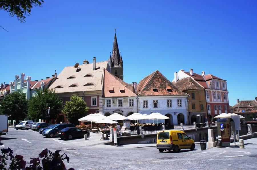 Recorre la Plaza Menor en Sibiu que está llena de cafés
