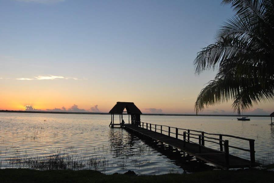 Contempla el atardecer desde un muelle en la laguna de Bacalar